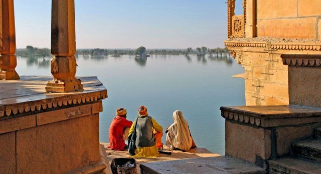 Three peopel sitting near the lake