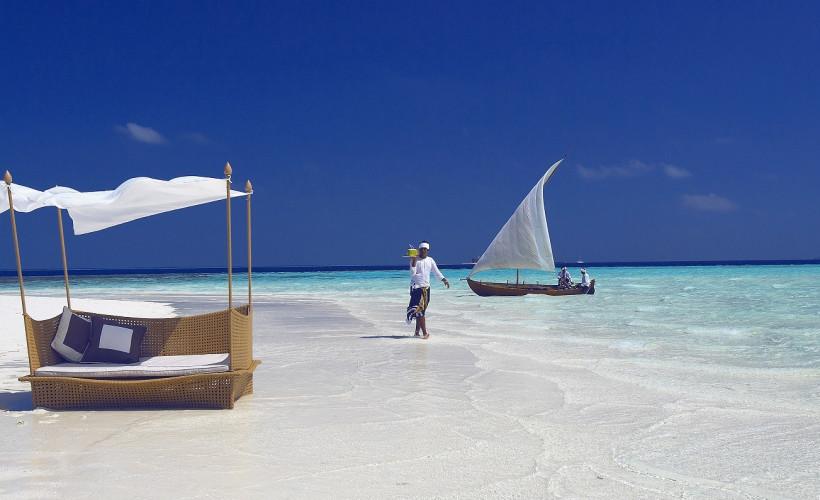 Person geht mit Getränken einen weißen Sandstrand mit Sonnenliege und Segelboot entlang