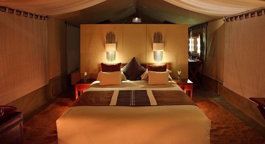 Beleuchtetes Schlafzimmer mit hergerichtetem Bett