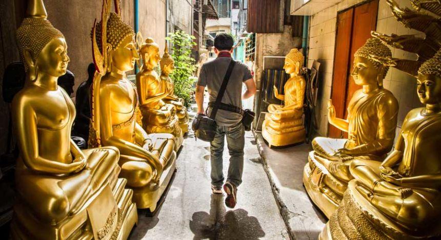 Mann läuft entlang goldener Buddha-Statuen