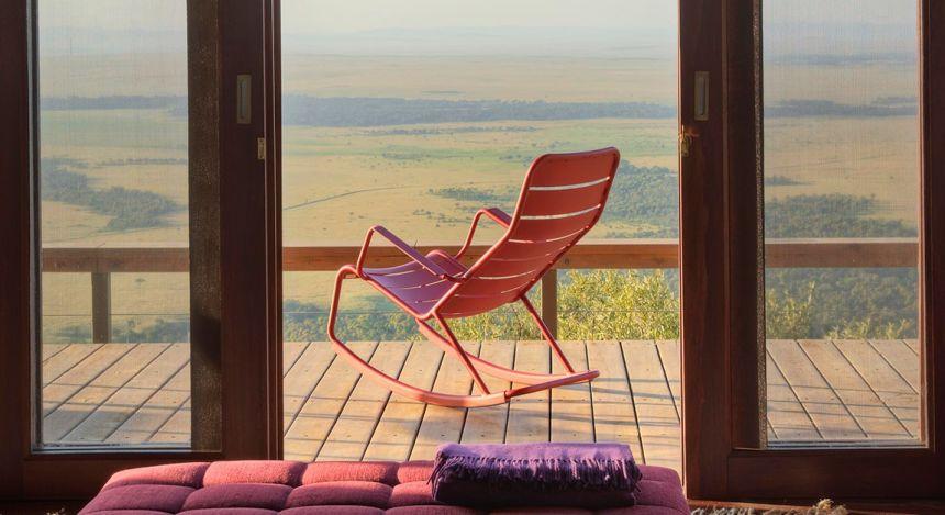 Schaukelstuhl auf einem Balkon mit Aussicht über die afrikanische Savanne im Hotel Angama Mara in Kenia