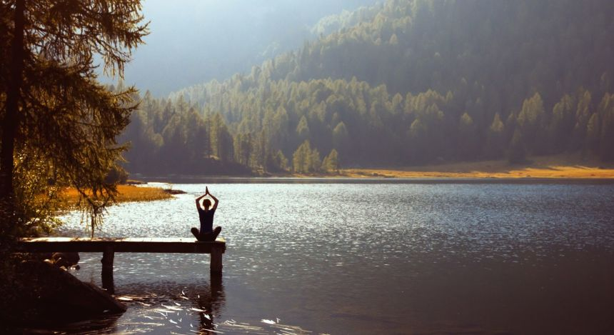 Person beim Yoga am See