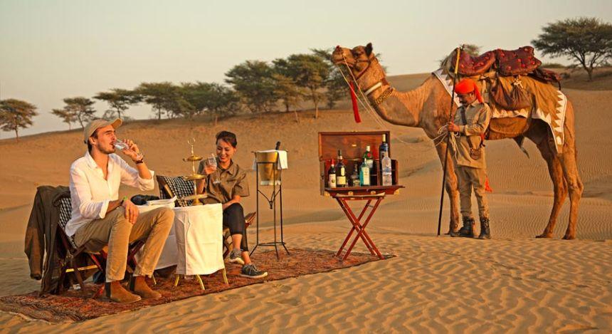 Paar trinkt in den Dünen der Wüste