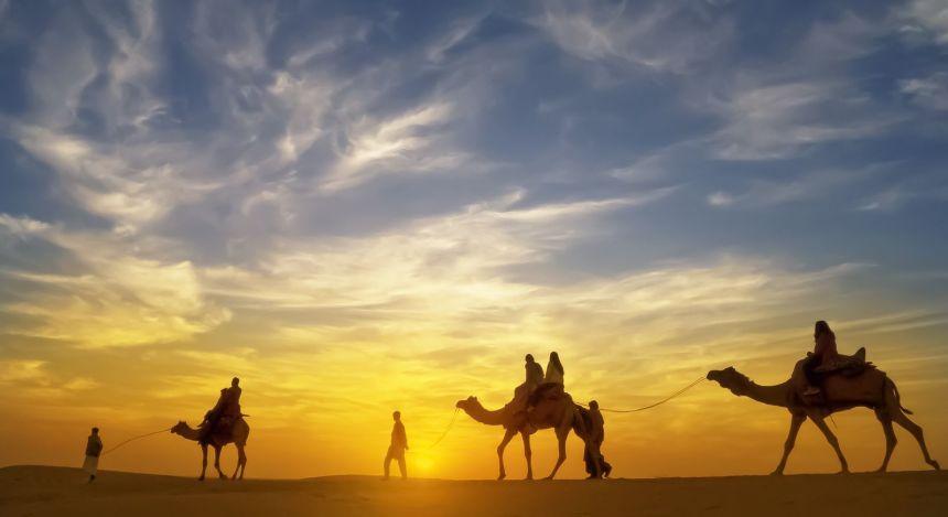 Menschen auf Kamelen vor Sonnenuntergang