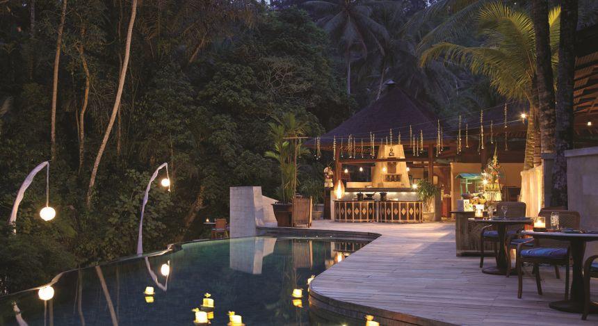 Pool mit Holzsteg vor abendlich beleuchtetem Haus