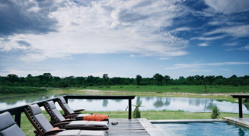 Swimmingpool mit Sonnenliegen in afrikanischer Wildnis, in Krüger, Südafrika