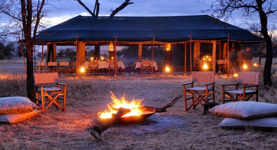 Zelt mit Tischen und Lagerfeuer in einem der Safari Camps