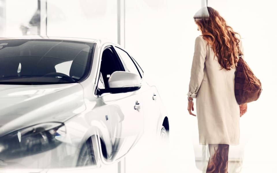 Kvinne ser på hvit Volvo
