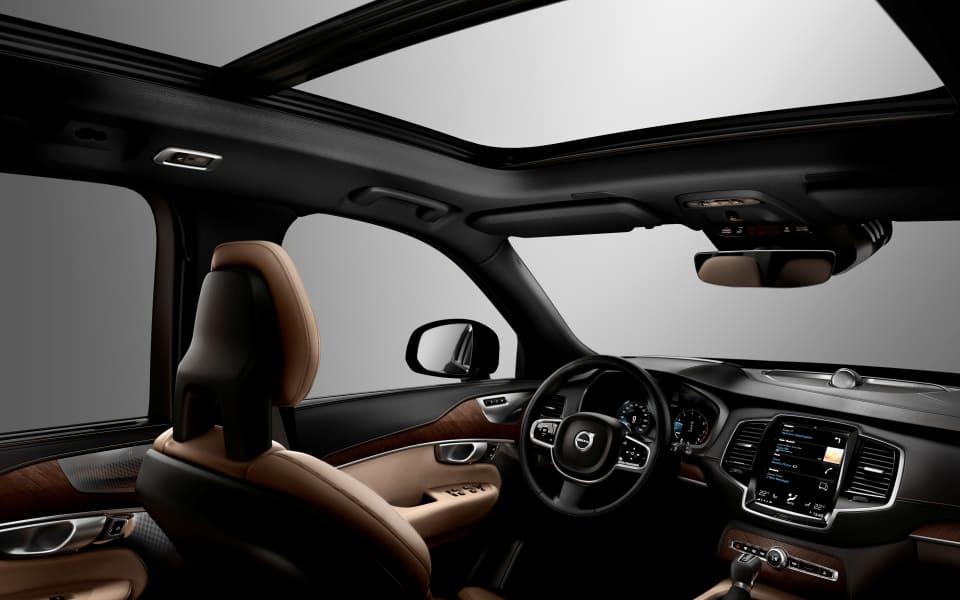 Interiørbilde fra Volvo XC90 med brunt skinninteriør, panaoramasoltak og mørke trepaneler