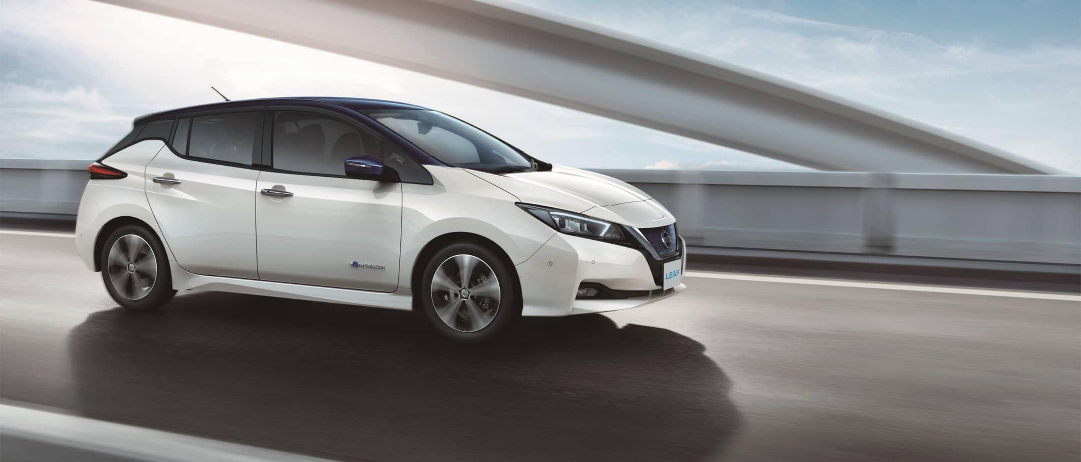 Hvit Nissan Leaf kjører på vei over bro