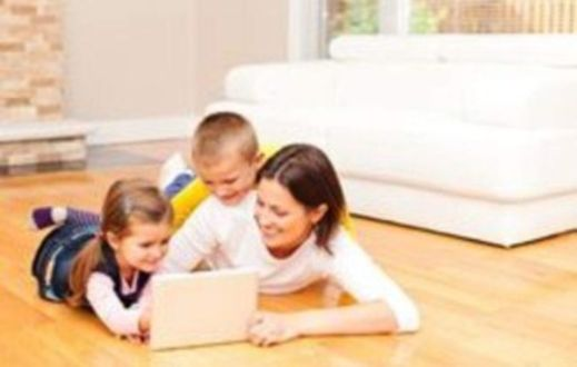 Carer and two children looking at a tablet