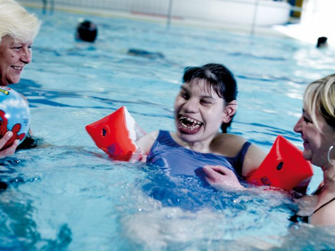 Swimming_disability_girl_with_floats.jpg