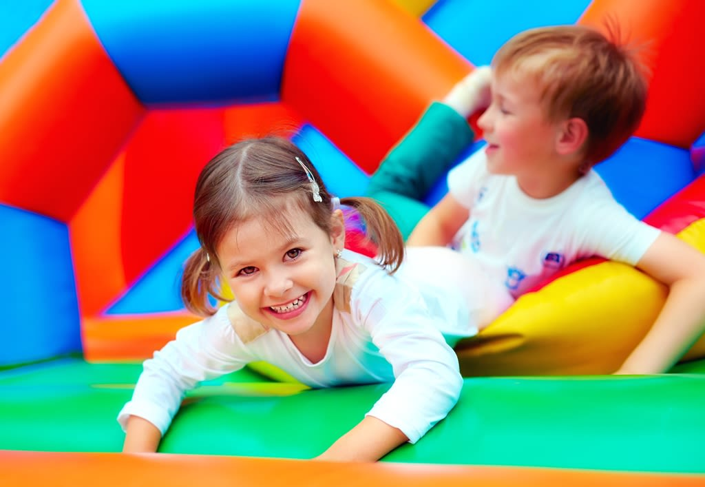 Children enjoying an inflatable party
