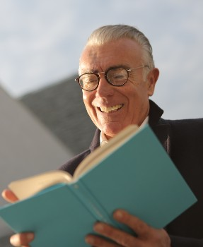 Man in black top holding blue book adult activities