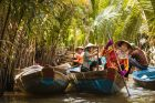 people with conical hats in boats rowing down the mekong delta