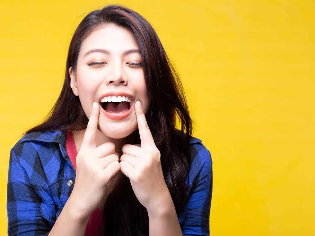 femme_sur_fond_jaune_pointant_son_sourire_avec_ses_doigts