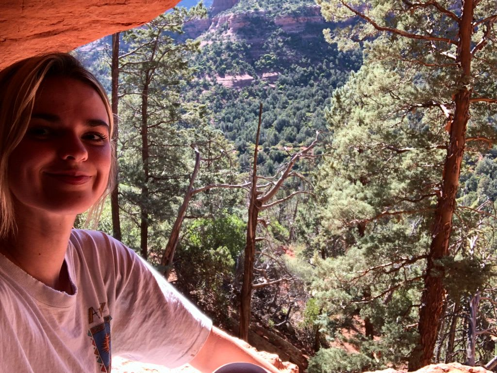 Lacy on perch overlooking Red Rock Country fromo the Soldier Pass Cave
