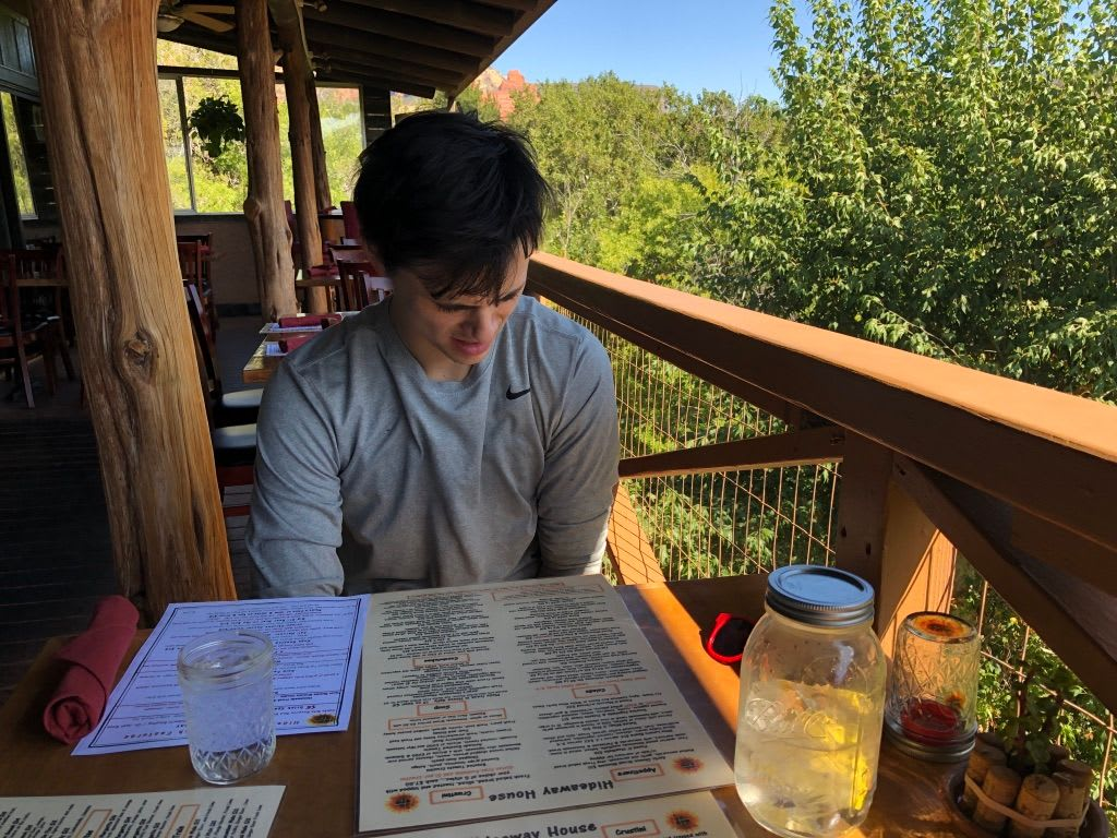 man sitting at a table looking at menu at the hideaway house in Sedona