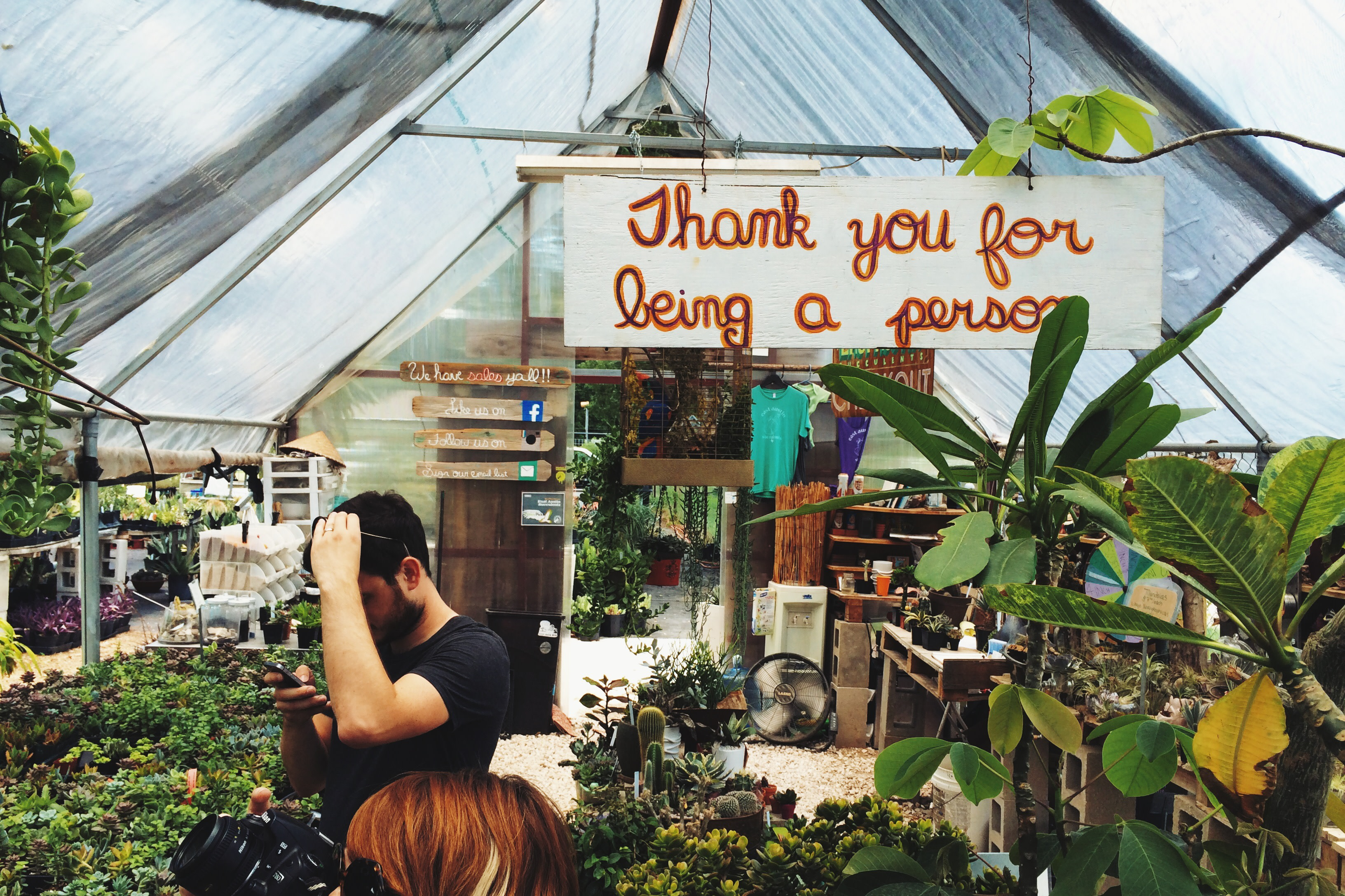 Two people browsing plants in a plant shop with a sign overhead that reads Thank you for being a person.