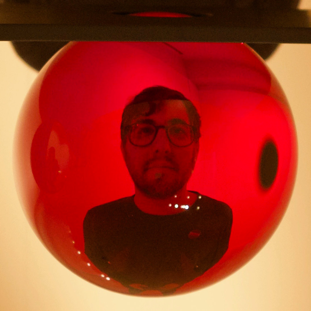 My head distorted as seen through a red glass sphere.