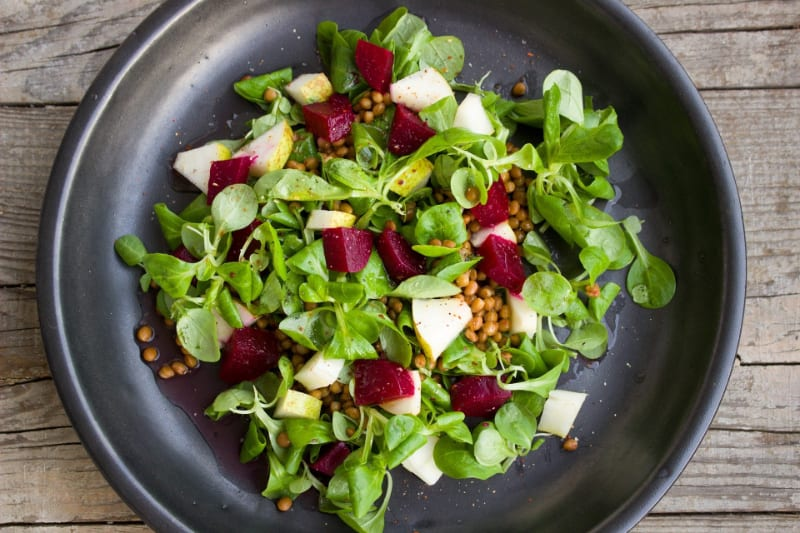 salad with beets in it on black plate on wood table