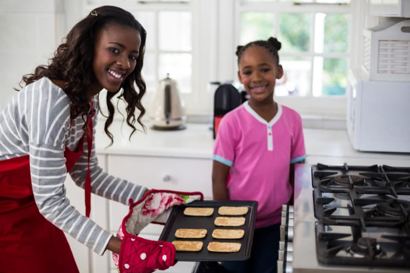 woman and girl cooking toast in a gas oven