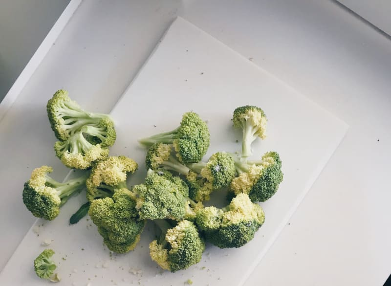 yellow and discolored broccoli on white cutting board