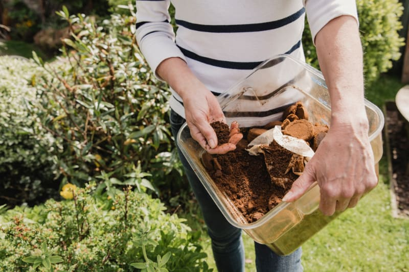 woman holding container with coffee grounds outside