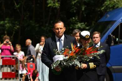 Prime Minister Tony Abbott carries flowers to place at the floral tribute to the victims of MH17 at Hilversum, Netherlands, 11 August 2014