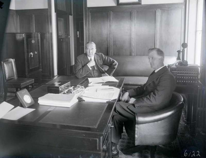 This is a black-and-white photograph showing Prime Minister Stanley Bruce and James Scullin seated at a desk in the prime minister's office in (Old) Parliament House, the day before Scullin was sworn in as the new Australian prime minister. Scullin is seated in a leather chair in front of the desk and Bruce is seated to his right at the side of the desk. Papers and writing materials cover much of the desk and a telephone is visible in the background. The room is wood panelled.