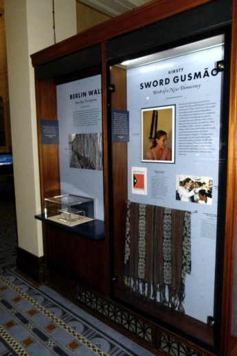 Side-by side in our Designing Democracy exhibition sits a fragment of the Berlin Wall and a tais mane woven by the people of Timor-Leste.