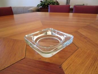 Glass ashtray on wooden desk.