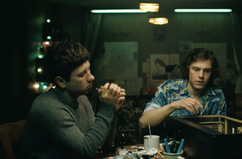 A scene from American Animals 2018 film showing two men sat at a table in a dark room.