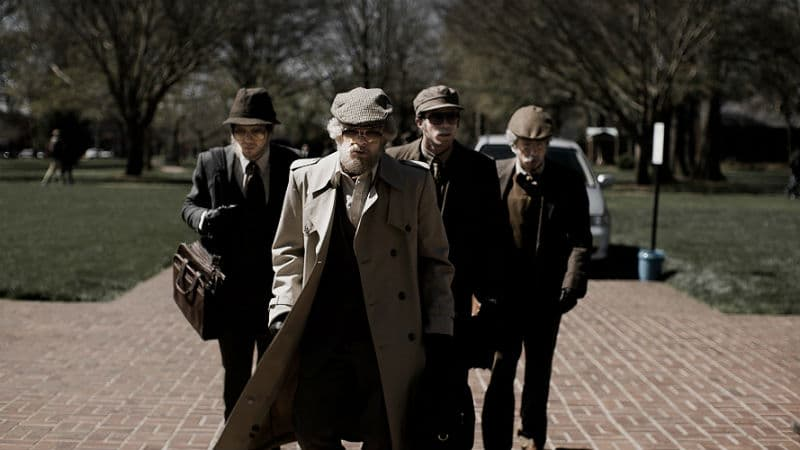 A Scene from the 2018 American Animals film showing a group of four disguised men, walking.