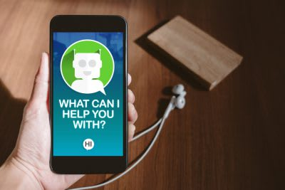 user hand holding mobile chatting with chat bot on phone screen at blur wood table,share video on social media concept,Digital marketing strategy