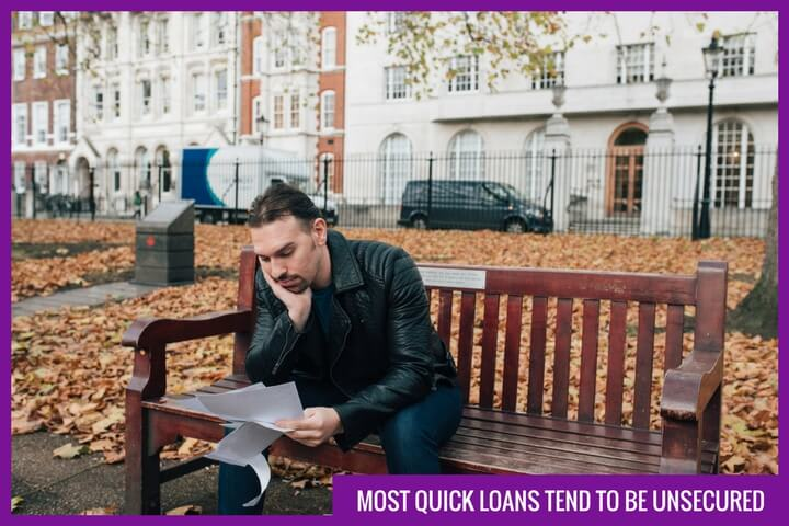 a handsome man is sitting on a bench and holding a pile of outstanding bills