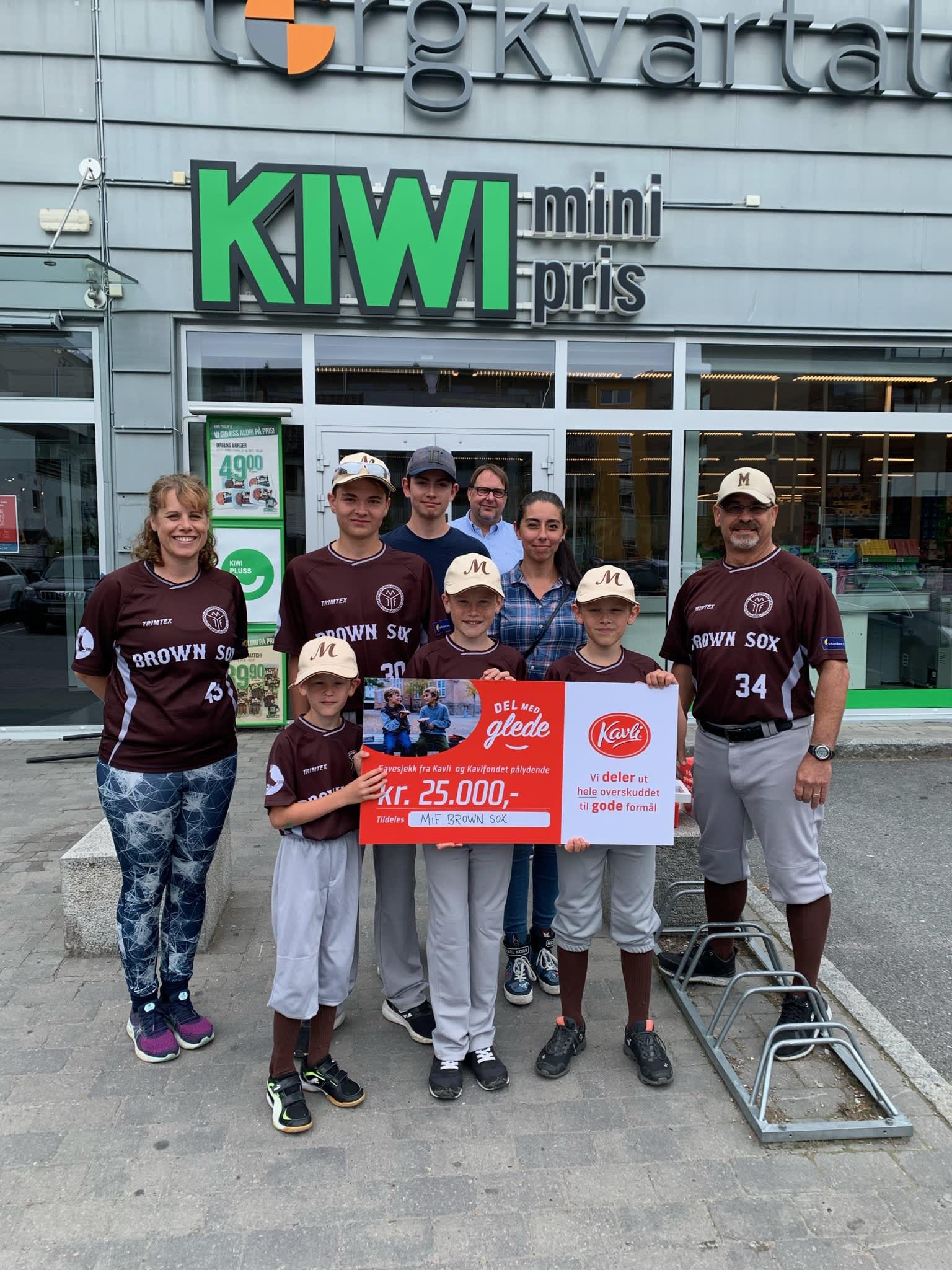Unge spillere i klubben holder gavesjekken fra Kavli pålydende 25.000 kroner, utenfor KIWI Mjøndalen.