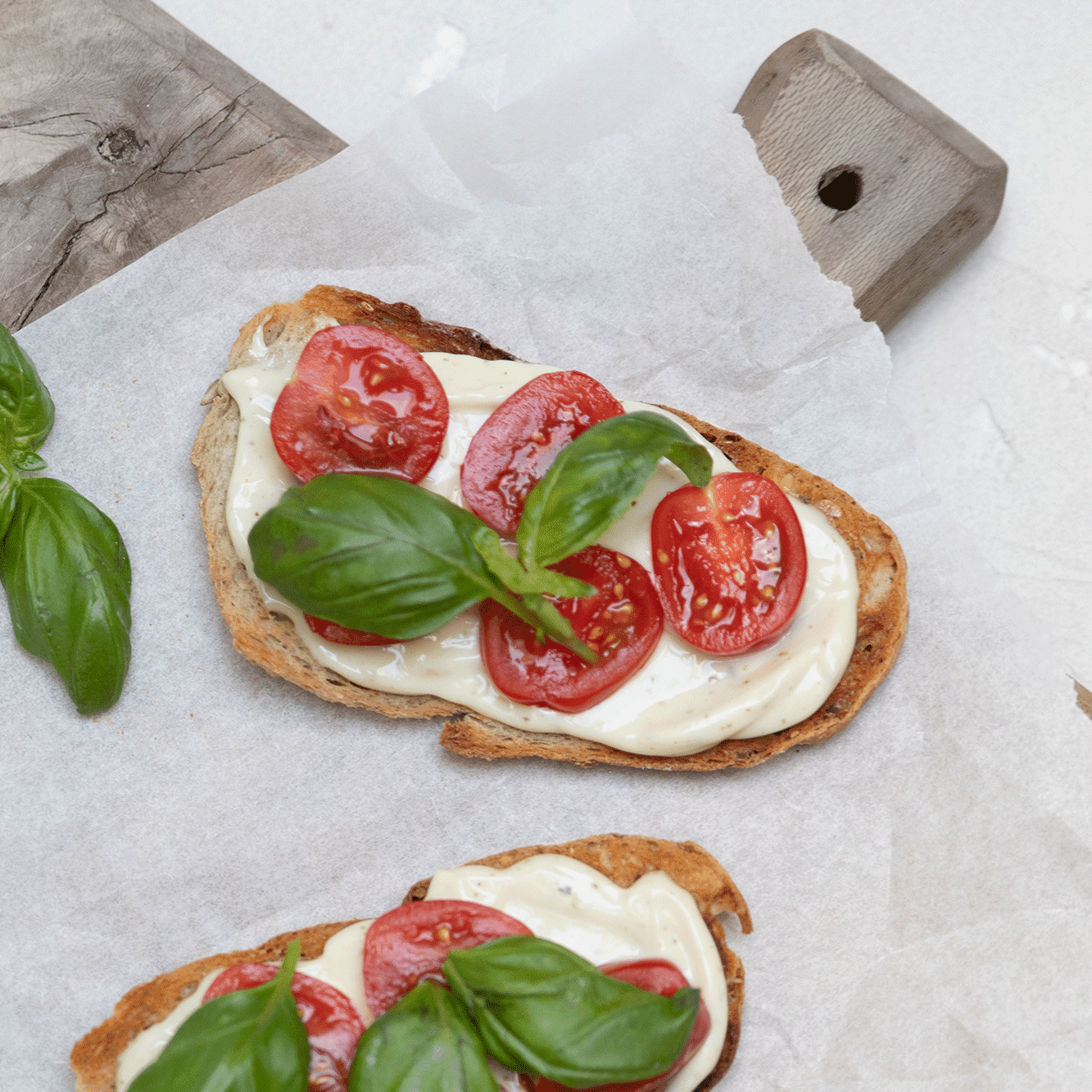 En bruschetta-aktig ristet surdeigsbrødskive med MagerOst, cherrytomater og basilikum.