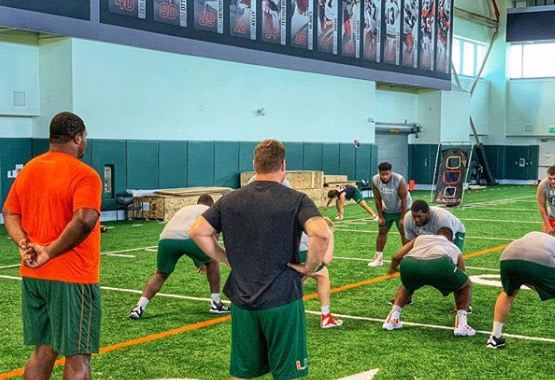 McKinnie and Romberg helping out Cane linemen on Monday