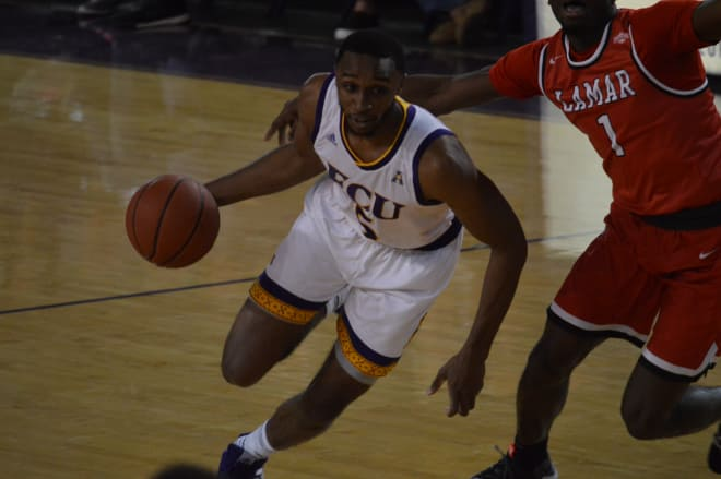 Ty Foster drives past Lamar's Mike Kolawole for two of his twelve points in ECU's overtime win over the Cardinals.