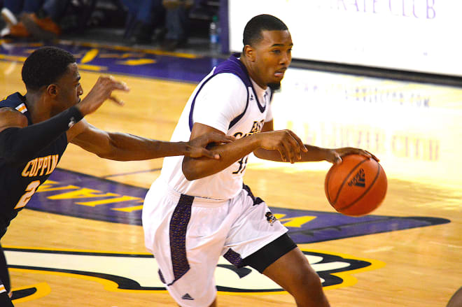 ECU center Charles Coleman drives past Coppin State's Kamar McKnight in Tuesday night's game in Greenville.