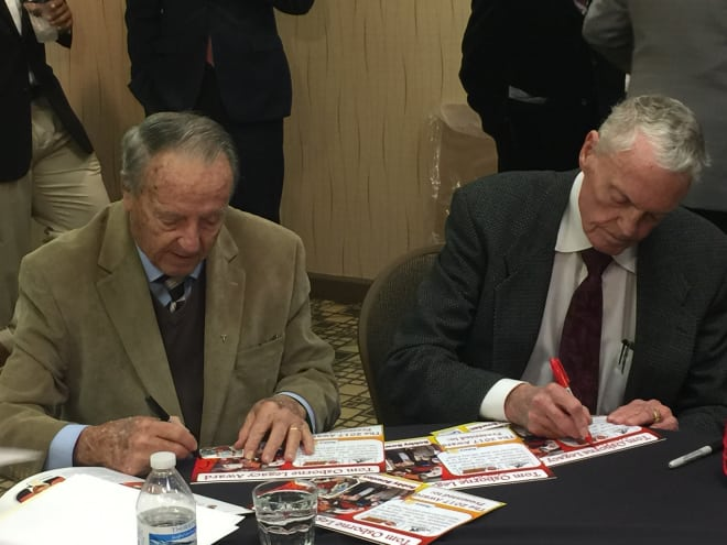 Coaching legends Bobby Bowden and Tom Osborne sign artifacts at the Outland Trophy banquet.