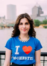 "Rachel stands infront of the Genesee River wearing a ""I Heart Rochester"" T-shirt"