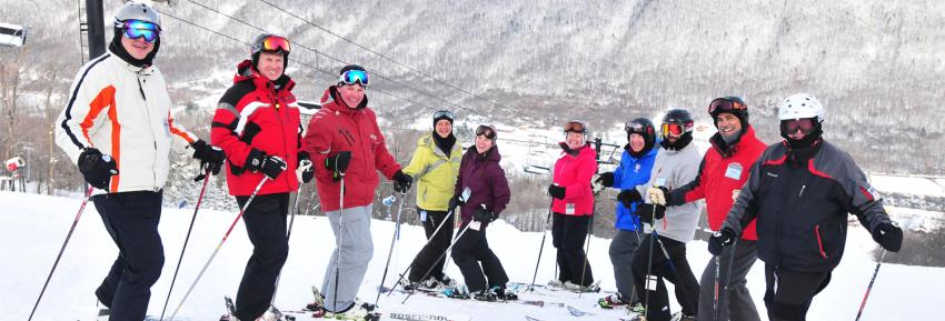 A group of Skiers pose for a photo on top of Bristol Mountain