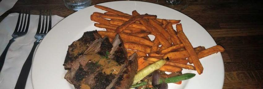 Steak drizzled with house made sauce and a side of veggies with sweet potato fries.
