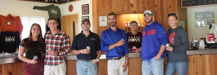 Young people dressed in casual attire line the bar at Naked Dove brewing with samples of beer in hand.