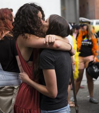 Two lesbian women embrace at Oakland Pride