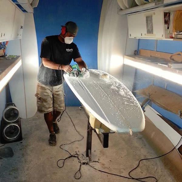 Rocky shaping a Mckinnon surfboard