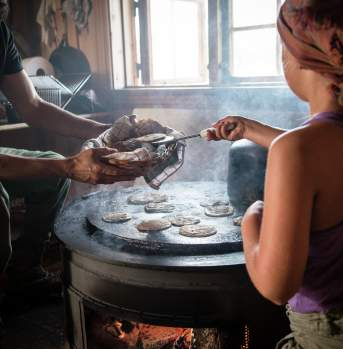 Girl cooking at the mountain farm