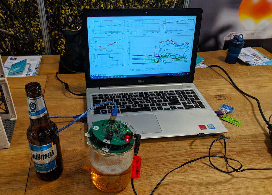 The e-nose device looks like a microchip. It's covering a glass of beer and plugged into a laptop via USB. The laptop shows a range of data, and a beer bottle sits next to the glass on a wood desk.